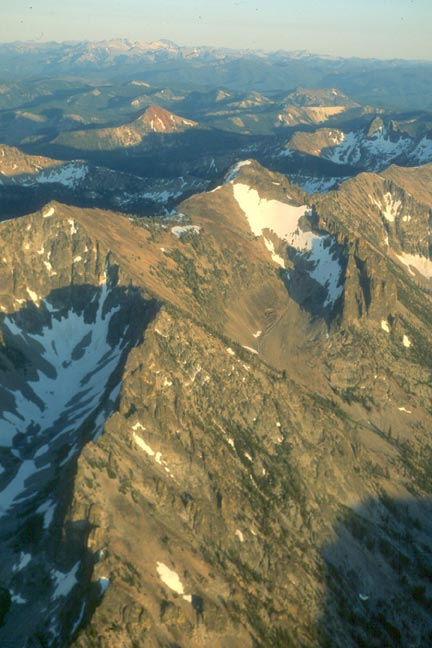 An aerial image of high rocky peaks laced with snow, draped in rich evening light and shadow.