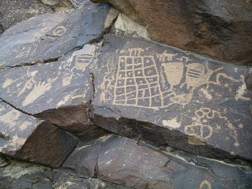 Ancient drawings of various patterns and shapes, adorn a large brown slab of rock.