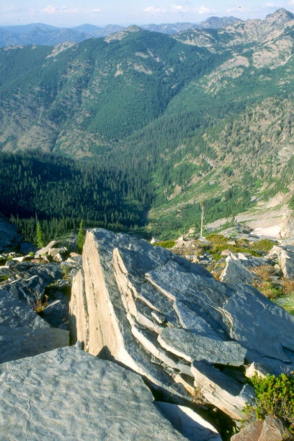 Looking down over a large rocky outcropping, to a forested valley far below.