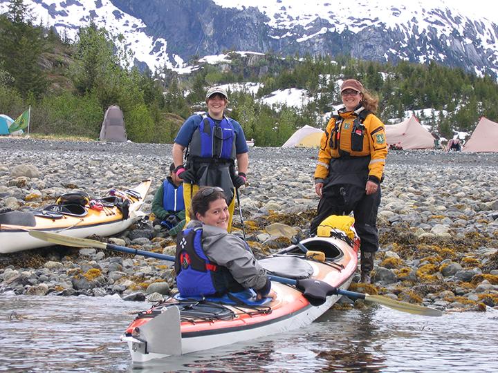 Women sea kayakers on a shore in Alaska