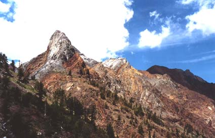 Tall rocky points of marbled red, yellow, and gray rock, rising above the forested slope below.