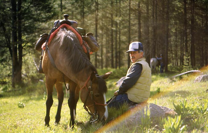 An outfitter sits on a rock next to his grazing horse.  A rainbow-colored lens flare appears in the foreground.