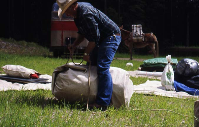 A man in a cowboy hat, packing a large canvas bag with equipment.