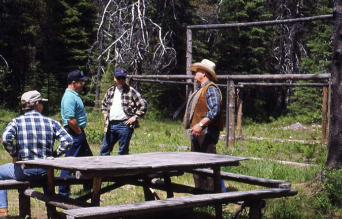 Four men standing around a table, with a large frame in the background along the edge of the forest.