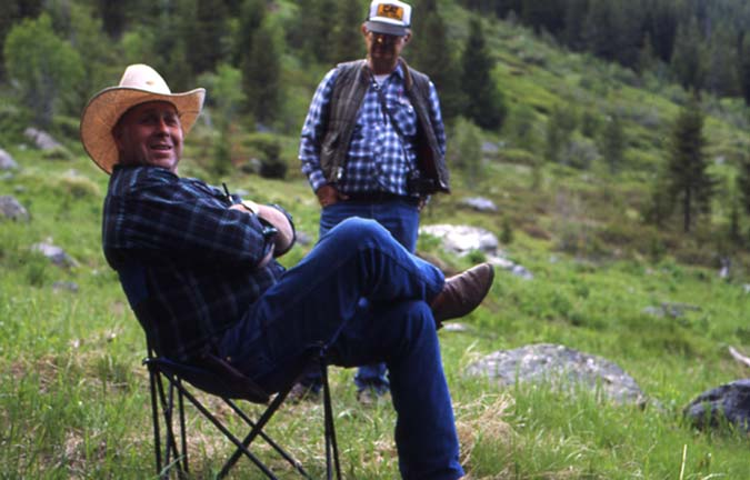 A man in a cowboy hat sitting in a grassy meadow on a camp chair, as another man walks past in the background.