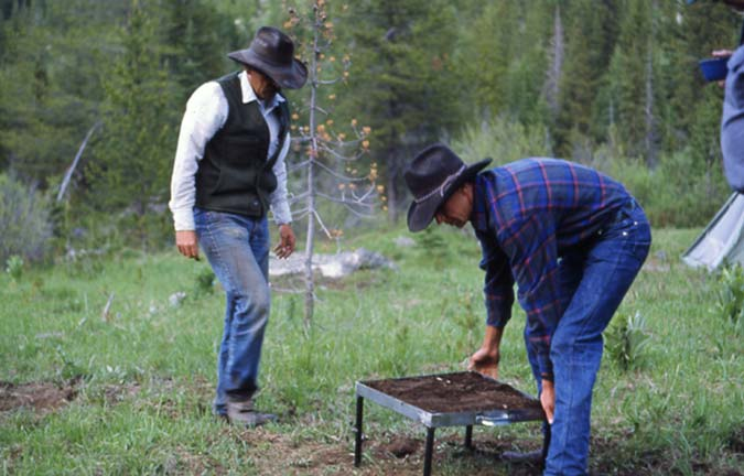 Two men in cowboy hats, moving a small fire grate.