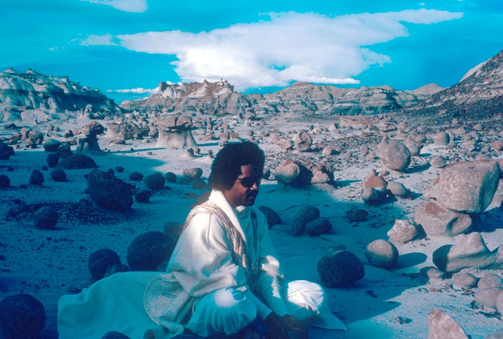An African-American man in a white robe, sitting in a desert landscape, surrounded by small boulders on a bed of white sand.