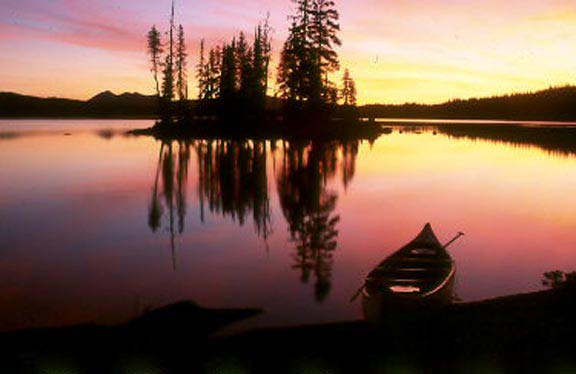 A brilliant yellow, pink, and purple sunset reflects off the lake behind a canoe beached on the shore.