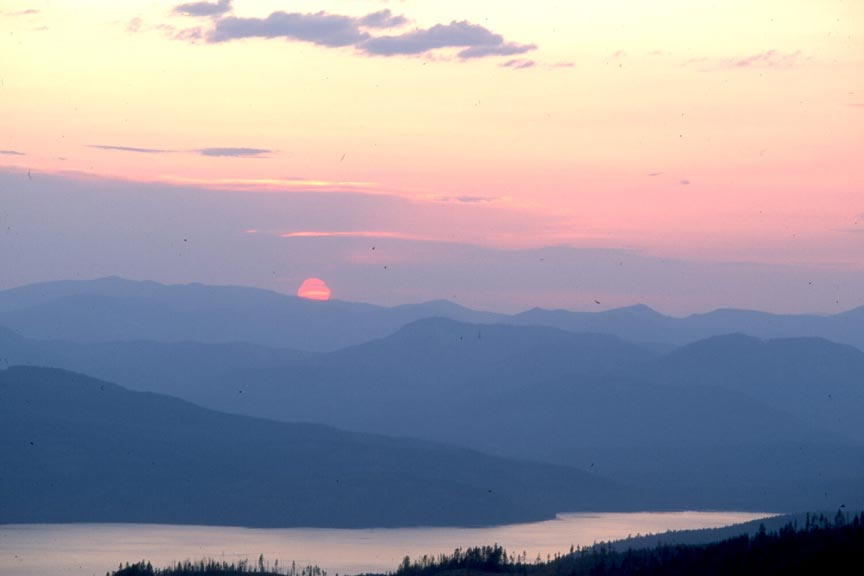 A tranquil scene of a pink sun setting over blue hazy hills, above a large lake reflecting a purple sky.