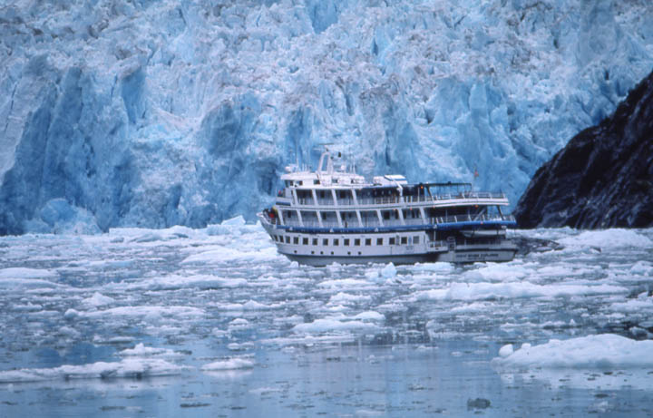 A large sight-seeing boat navigating through brash ice near the massive jagged blue face of a tidewater glacier.