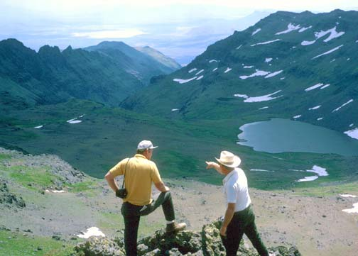 Two men standing high on a rock outcropping, looking down over a high alpine bowl, dotted with patches of spring snow.