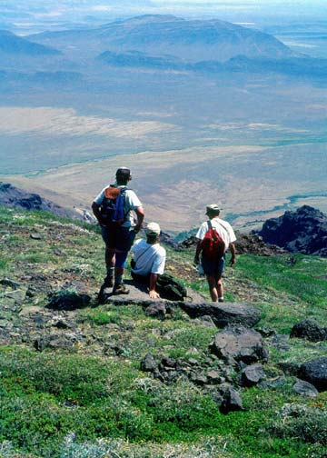 Three hikers standing high on an alpine slope, looking down over a barren desert valley far below.