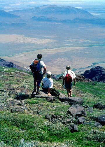 Three hikers standing high on an alpine slope, looking down over a barren desert valley far below.