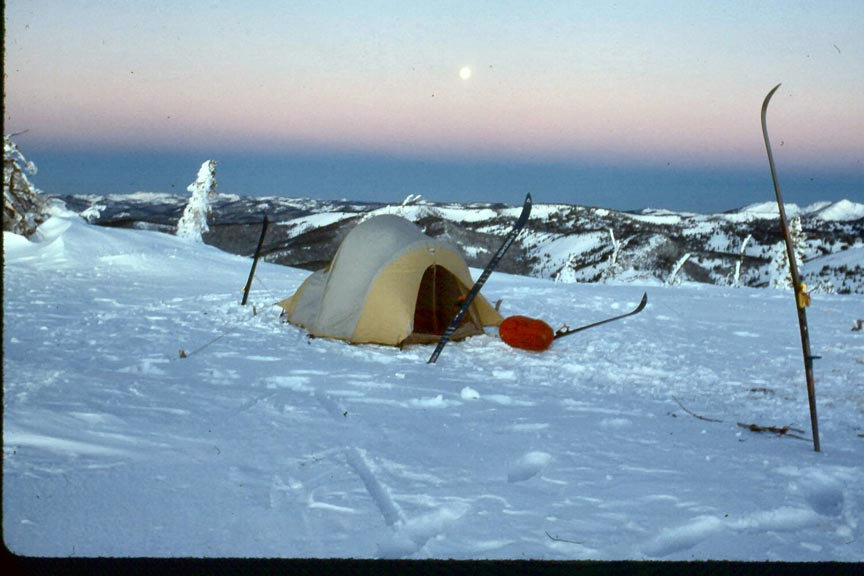 A winter scene of a yellow tent surrounded by snow, surrounded by snow covered mountains, under a pink sky with a full moon.