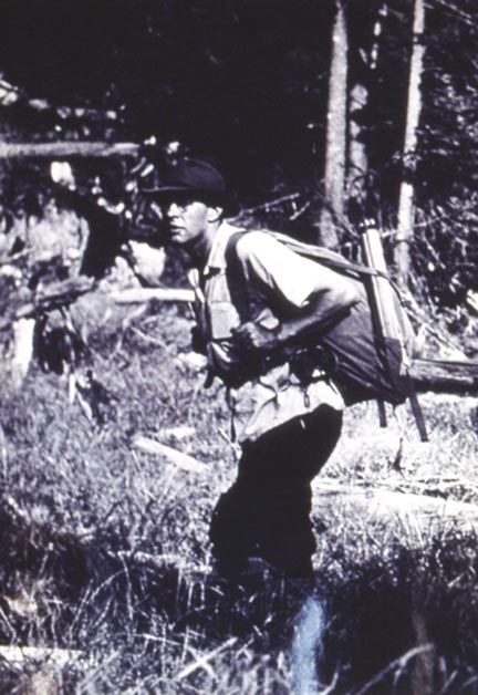 A vintage black and white image of a man with a backpack.