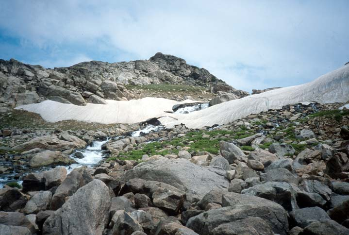 A small stream of melt-off flowing from a large patch of snow, past a patch of green grass and into a jumbled pile of boulders below.