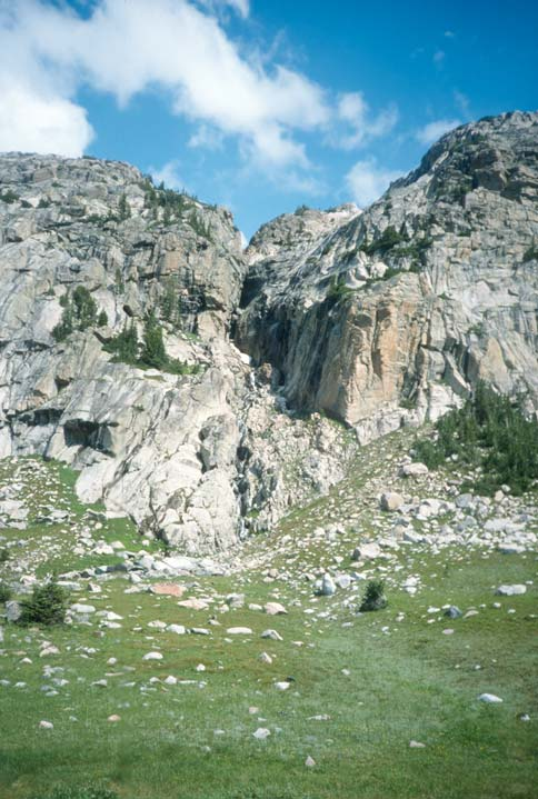 Tall gray cliffs rise from a green grassy slope littered with fractured rock.