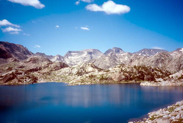 An alpine lake reflecting the brilliant blue of the sky, surrounded by rugged peaks, streaked with snow.