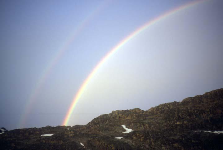 A brilliant double-rainbow against a gray sky, rising high over a ridge of black rock.