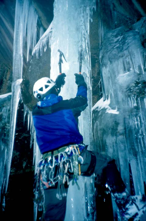 A climber in a blue jacket, clinging to a narrow column of clear ice, on a background of jagged icicles and rock.
