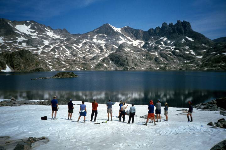A small group of hikers standing on a large patch of snow along the edge of a blue lake, rugged peaks laced with snow rise from the far shore.