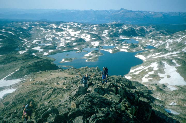 Looking down to three hikers ascending a rocky ridge, an expanse of open rock lies far below, mottled with patches of snow around a small lake.
