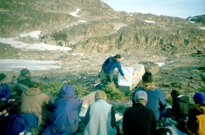 A man giving an outdoor presentation to a small group of hikers, rocky cliffs rising in the background.
