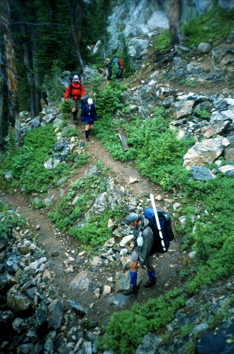A small group of backpackers traverse tight switchbacks along a narrow rocky trail, bordered by lush green brush.