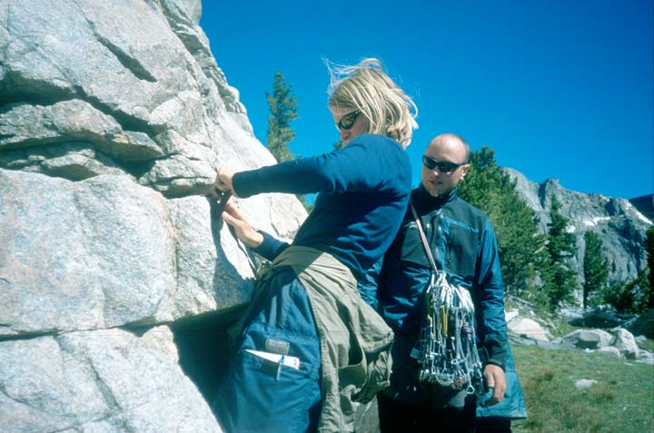 A man and a woman in climbing gear, practicing climbing technique at the base of a rock face.