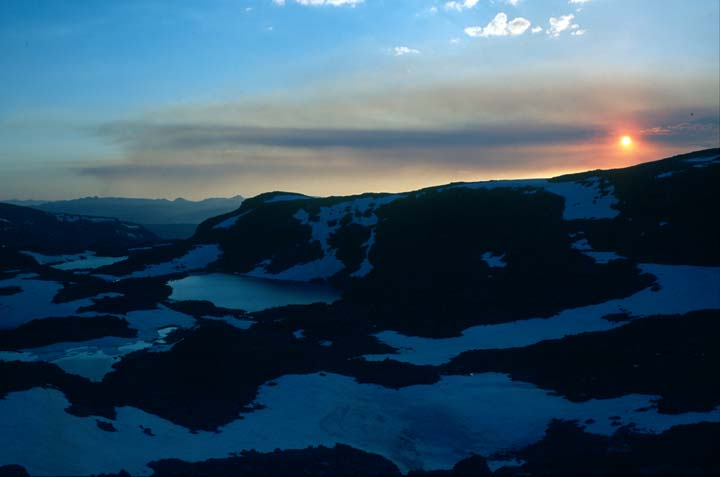 A fiery orange ball setting along the horizon over an alpine bowl drenched in deep blue shadow.