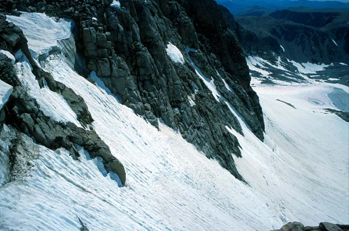 Looking into a rock face rising from deep snowpack below.