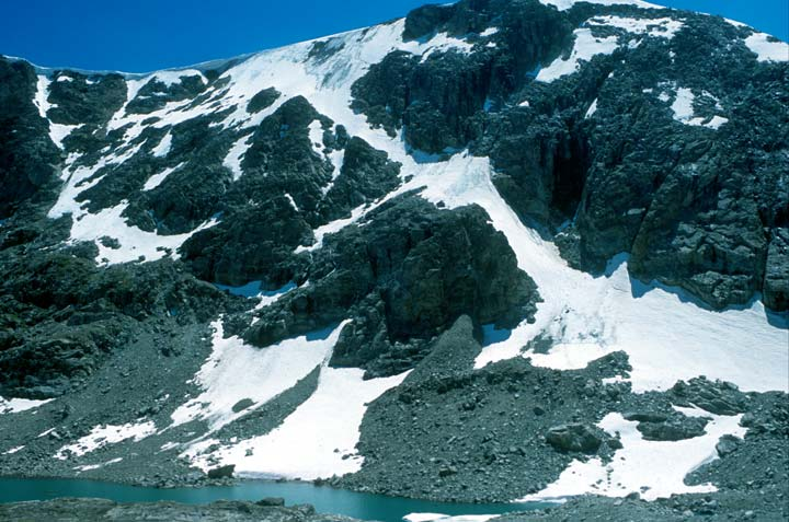 A rugged rocky face laced with snow, rising from the far side of a small strip of water below.