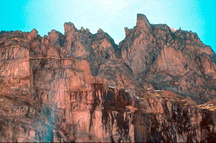 A jagged face of rugged rock, rising high towards an empty blue sky.