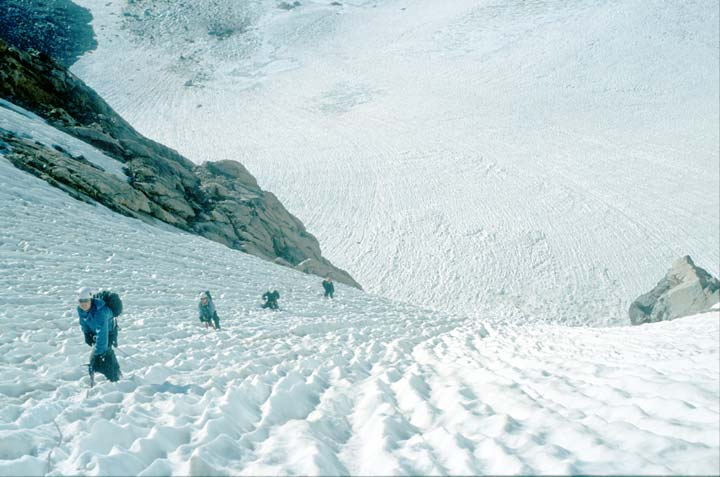 Four climbers in blue jackets ascending a steep snow-covered slope. An open ice field far below stretches away in all directions.