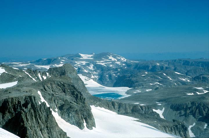 Looking out over a massive expanse of rugged alpine terrain, high rock faces jutting from the snowpack below.