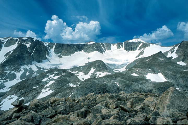 Jagged snowcapped peaks appear behind a large boulder field.