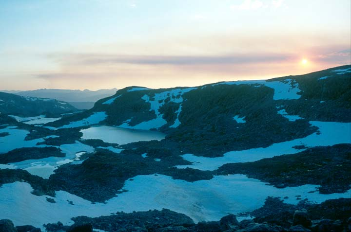 The setting sun settles over an alpine ridge, a small frozen lake below lies surrounded by large patches of snow and bare rock.