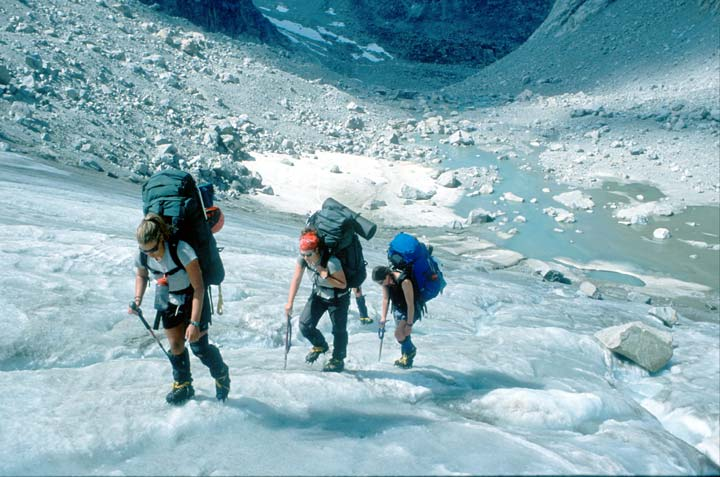 Three backpackers wearing crampons, ascending a section of gray glacier ice above a bloulder-strewn valley.