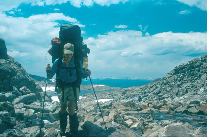 A woman wearing a large backpack, standing in a rocky draw near a small stream. A deep blue sky mottled with puffy white clouds, rises in the background.