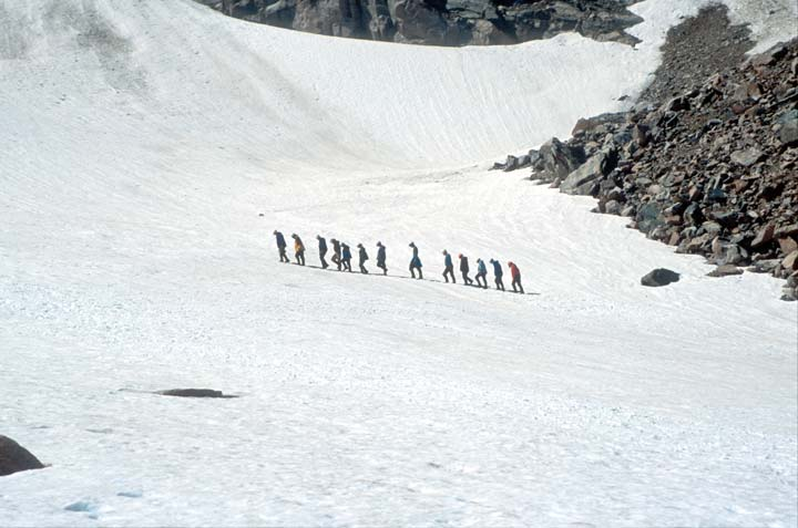 A group of climbers traversing a large snowfield at the base of a rocky face.