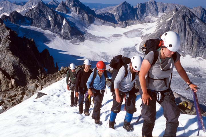 A teenage girl with helmet and ice axe leads four other mountaineers up a snowy slope.