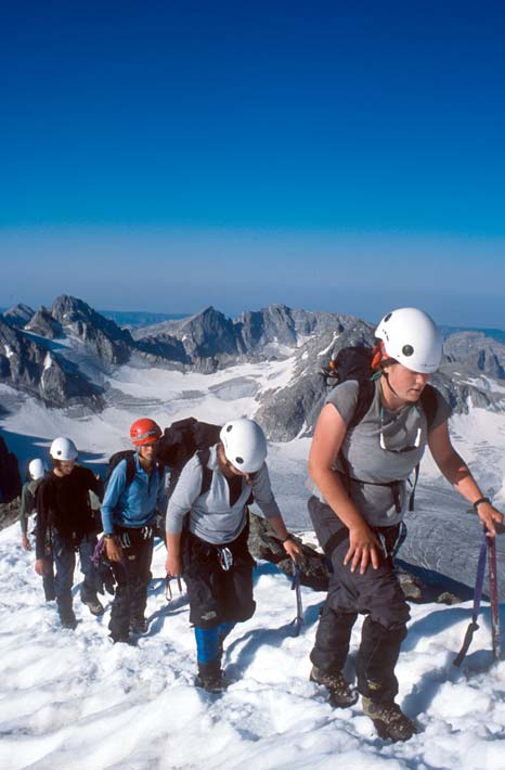 Four climbers wearing helmets with climbing gear and ice axes, high on a ridge overlooking a rugged ice field below punctuated with jagged rocky peaks.