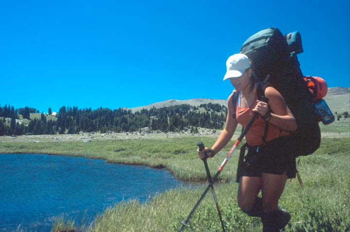 A woman wearing a large backpack, hiking along the grassy shore of a small blue lake.