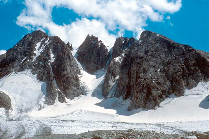 High rock faces rising from a snowfield, bordering a narrow snow chute leading high into the jagged peaks.