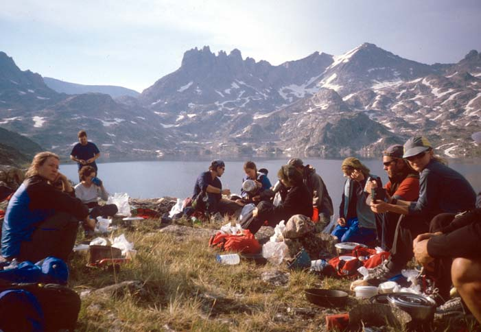A large group of hikers gathered around cooking equipment, looking out over a large blue lake in the background, surrounded by high rocky peaks laced with snow.