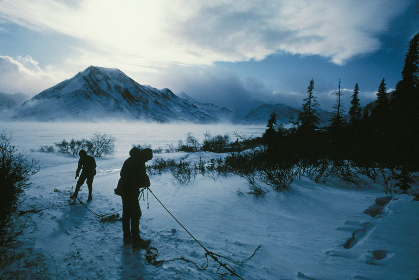Two men untangle a string of dog harnesses along the edge of an open plane, blowing snow rising around the base of the surrounding mountains.