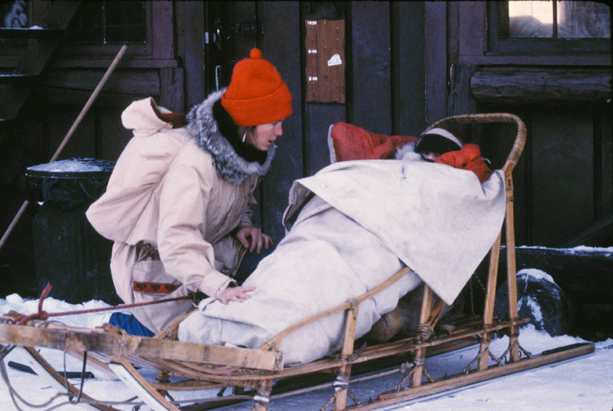 A woman kneeling next to a sled, containing a child wrapped in a blanket.