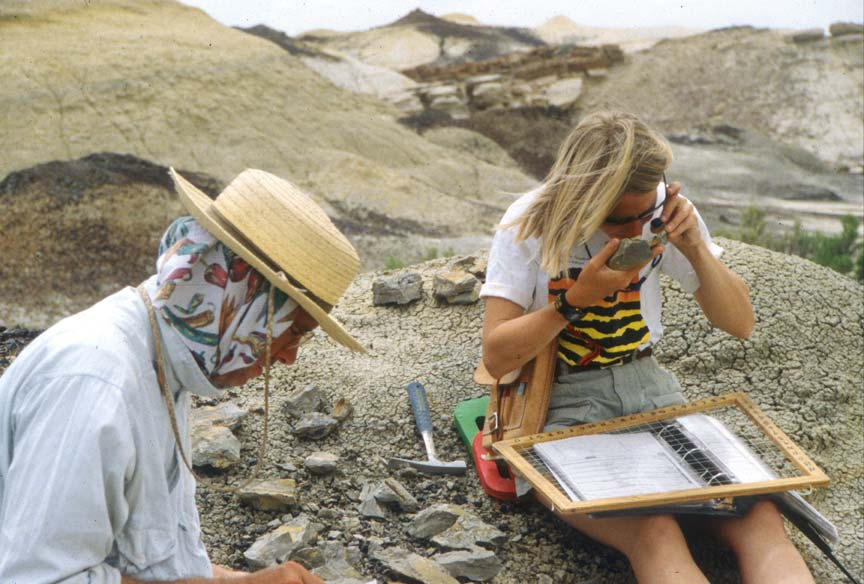 Two archeologists carefully examining small artifacts from the rocky landscape.