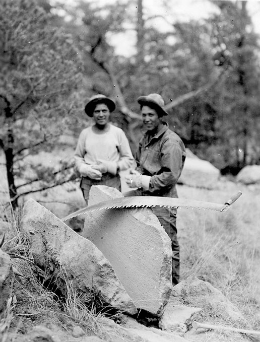 A vintage black and white photograph of two men standing next to a hand saw, and a large boulder cut in two.