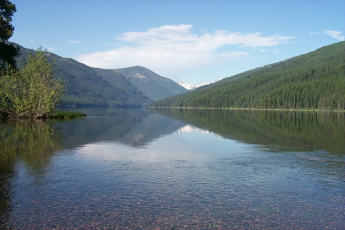 Glassy waters of a large forest lake, reflecting the surrounding green hills and light blue of the sky above.